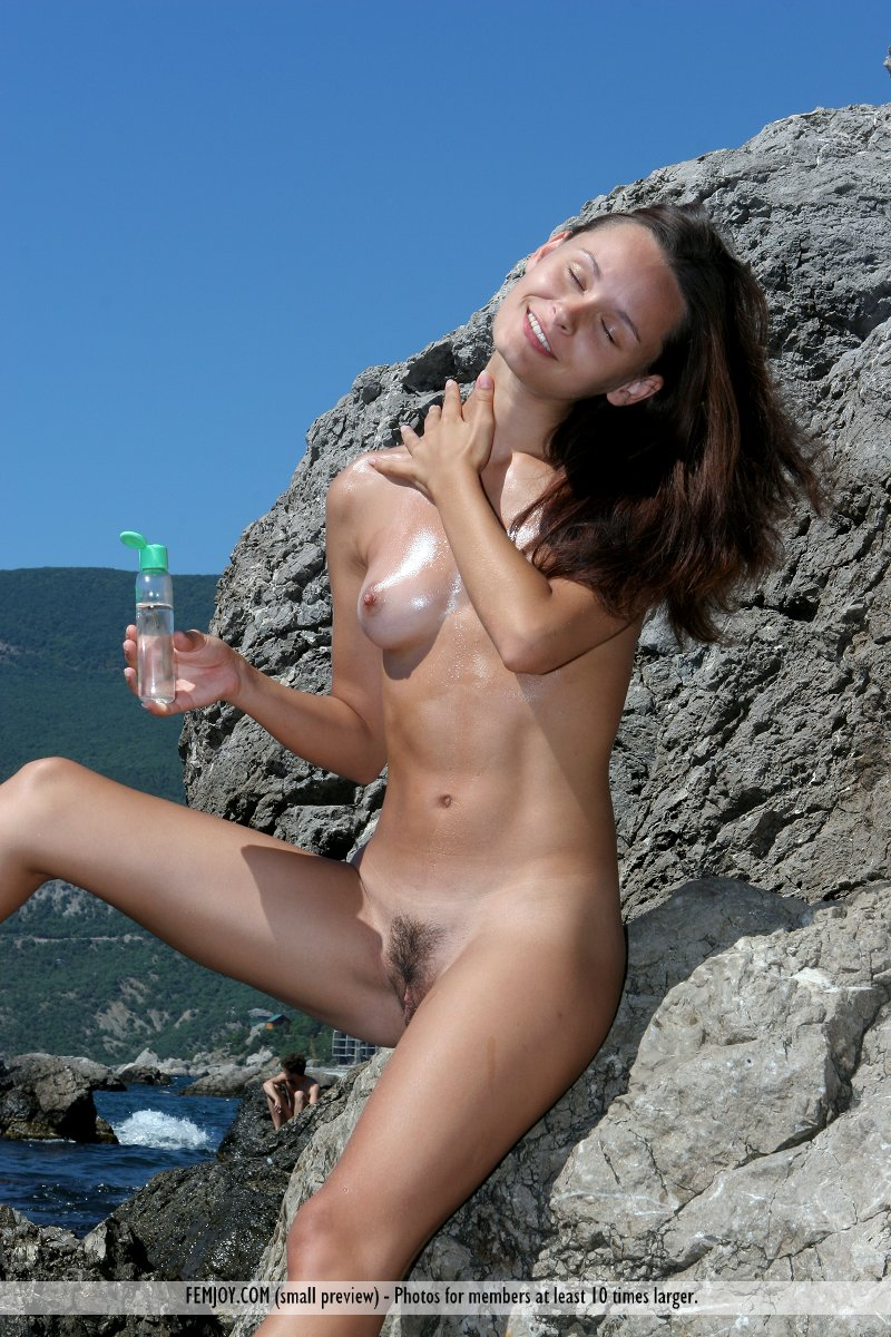 Girl with hairy pussy posing on sea cliffs